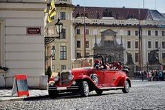 Rode toeristische oldtimer van bij het begin van de 20ste eeuw op historisch cobbled weg in Praag Stock Afbeeldingen