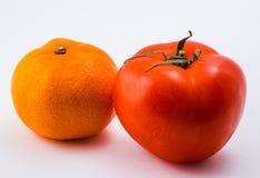 rode tomaat en oranje mandarijn op een witte achtergrond Stock Foto's