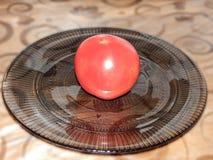 Rode tomaat op een plaat op de lijst stock foto's