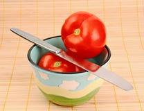 Rode tomaten in een kom. Het mes van de lijst. Stock Afbeelding