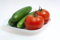 Rode tomaten en groene komkommers op witte plaat Royalty-vrije Stock Afbeeldingen