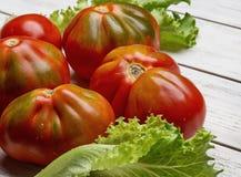 Rode tomaten en salade op witte houten raad Stock Fotografie