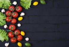 Rode tomaten met greens en citroenen op een zwarte houten achtergrond Een samenstelling van groenten en vruchten op een houten ac stock fotografie