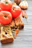 Rode tomaten op een houten raad met kruiden Stock Foto's