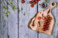 Rode tomatenkers met een knipselraad op een houten achtergrond Stock Foto