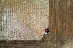 Rode tractor die aan de lentegebied werkt, satellietbeeld royalty-vrije stock afbeeldingen