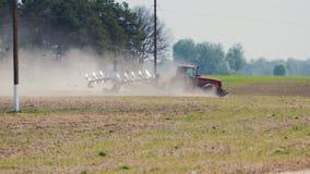 Rode tractor die de grond in heet droog weer op de achtergrond van de polen van de machtslijn cultiveren stock videobeelden