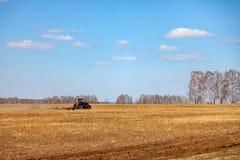 Rode tractor met een gesleepte ploeg voor het maaien van en het wieden van gebieden voor de agro-industrie van gele kleur onder d royalty-vrije stock foto's