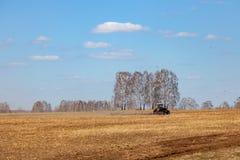 Rode tractor met een gesleepte ploeg voor het maaien van en het wieden van gebieden voor de agro-industrie van gele kleur onder d stock afbeelding