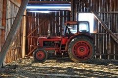Rode tractor in schuur stock fotografie