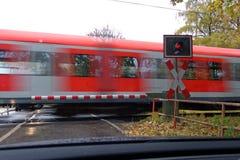 Rode trein die langs bij spoorweg meeslepen die met poorten kruisen stock fotografie