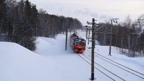 Rode treinritten door het sneeuw de winterhout stock footage