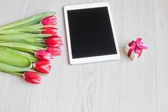 Rode tulpen, giftdoos met een rode boog en tablet Stock Foto