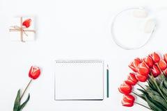 Rode tulpen, kleine giftdoos, hoofdtelefoons en notitieboekje Royalty-vrije Stock Afbeelding