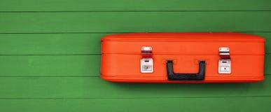 Rode uitstekende koffers met zwart handvat op de houten groene achtergrond Stock Foto