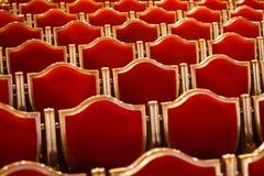 Rode uitstekende stoelen in het theater stock foto's
