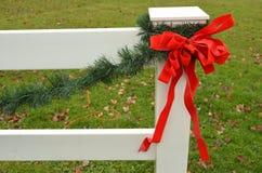 Rode van de de boog groene pijnboom van het vakantielint de slinger witte omheining Stock Foto's