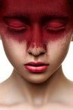 Rode verf op gezicht van schoonheidsmodel stock afbeeldingen