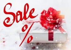 Rode Verkoop % die met witte giftdoos, rode boog op sneeuw met bokeh en sneeuwval van letters voorzien Valentijnskaartendag coupo royalty-vrije stock foto