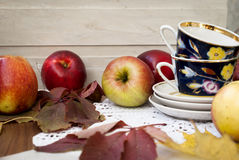 Rode verse appelen met bladeren en koppen voor thee Royalty-vrije Stock Afbeeldingen