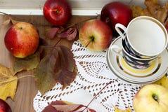 Rode verse appelen met bladeren en koppen voor thee Royalty-vrije Stock Foto's