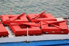 Rode vierkante reddingsboten met peddels op dak van oude plezierboot stock afbeelding