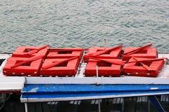 Rode vierkante reddingsboten met peddels op dak van oude plezierboot royalty-vrije stock fotografie