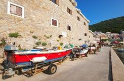 Rode vissersboottribunes op de kust Stock Foto