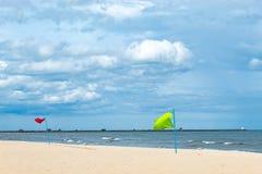 Rode vlag en groene die vlag op het strand door het overzees wordt geborduurd stock afbeeldingen