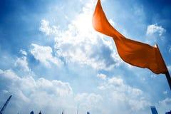 Rode vlag op een achtergrond van de donkerblauwe hemel met wolken Royalty-vrije Stock Afbeeldingen