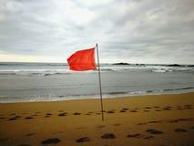 Rode vlag op het strand Stock Afbeelding