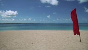 Rode vlag op wit zandstrand op tropisch eiland stock videobeelden