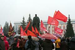 Rode vlag van Communistische partij van de Oekraïne tegen een monument aan Lenin stock foto