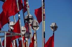 Rode vlaggen in de wind stock afbeeldingen