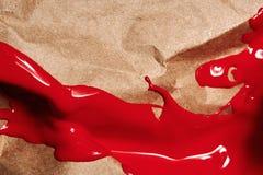 Rode vloeibare Verf op bruine ambacht gerimpelde Verf stock foto's