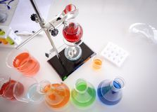 Rode vloeistof in glas het testen fles op het rek stock foto's