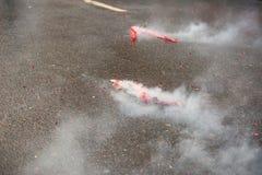 Rode voetzoekers die met rook op het asfalt exploderen royalty-vrije stock fotografie