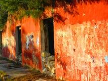 Rode voorgevel van een geruïneerd huis bij de ingang van een verlaten Hacienda stock foto's