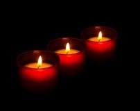 Rode votive kaarsen die op de donkere, zwarte achtergrond branden Royalty-vrije Stock Foto