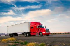 Rode vrachtwagen die zich op een weg beweegt Stock Afbeelding