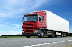 Rode vrachtwagen met witte aanhangwagen over blauwe hemel stock foto