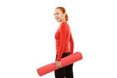 Rode vrouw met yogamat Stock Foto's