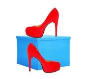 Rode vrouwenschoen en blauwe die giftdoos op wit wordt geïsoleerd Royalty-vrije Stock Foto's