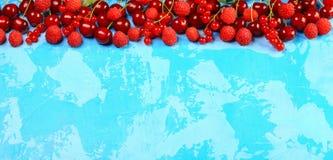 Rode vruchten en bessen als achtergrond Rijpe rode aalbessen, aardbeien, frambozen, kersen op een blauwe achtergrond Bessen bij g royalty-vrije stock fotografie