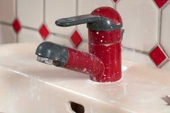 Rode vuile waterkraan stock foto's