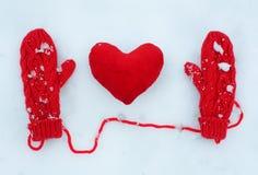 Rode vuisthandschoenen en pluche decoratief hart op sneeuw stock afbeelding
