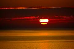 Rode Vuurtoren met Lichtstraal bij Zonsondergang De bovenkant Royalty-vrije Stock Afbeeldingen