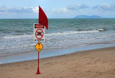 Rode waarschuwingsvlag op strand met Gevaarsteken stock foto's