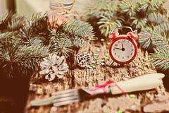 Rode wekker op houten achtergrond met groene takken van pijnboom Stock Foto