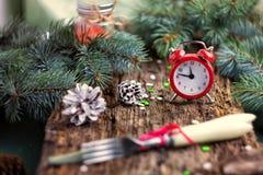 Rode wekker op houten achtergrond met groene takken van pijnboom Stock Afbeelding